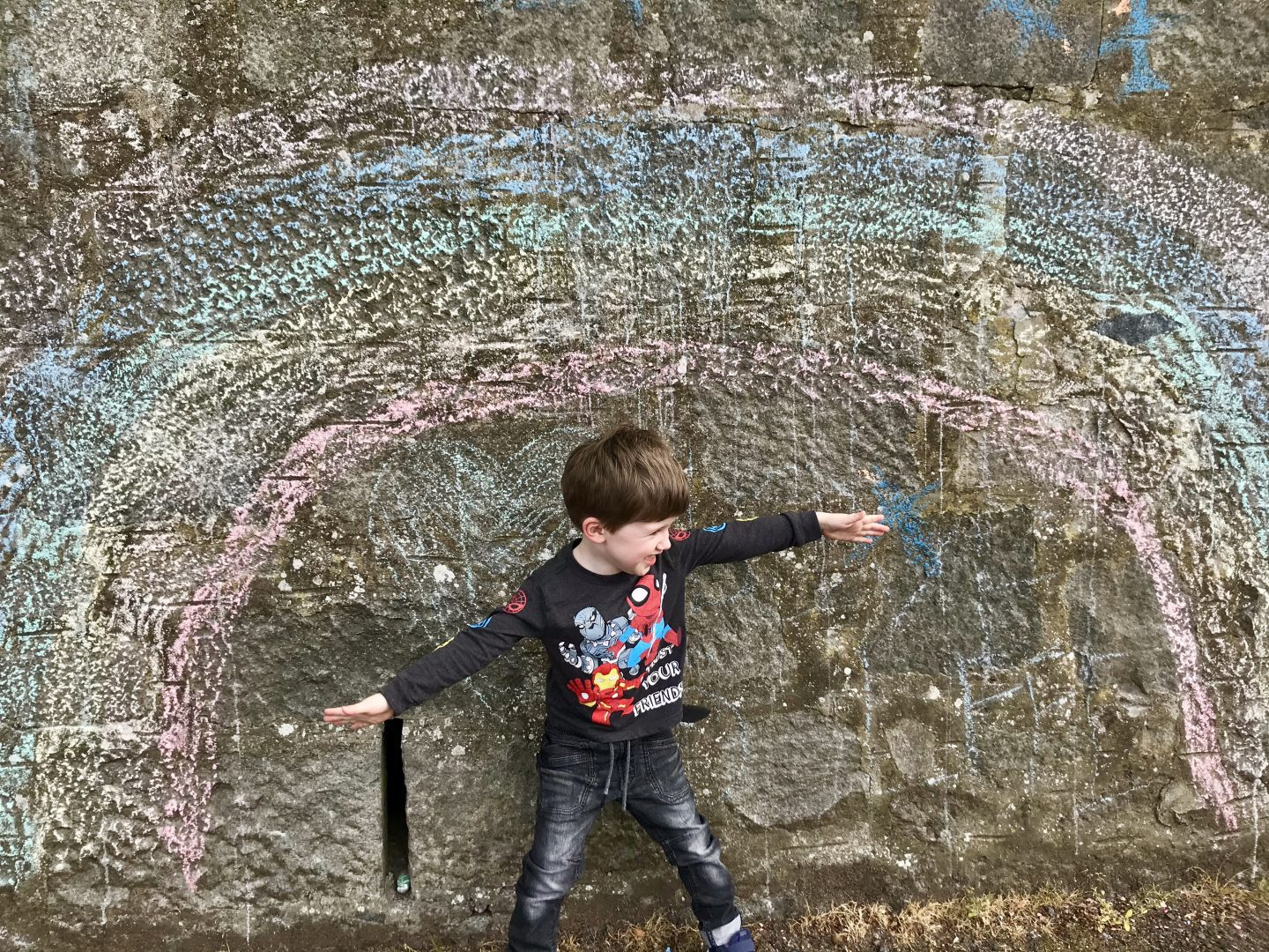 A boy standing in the middle of a giant rainbow drawn on a brick wall in chalk, with his arms spread open