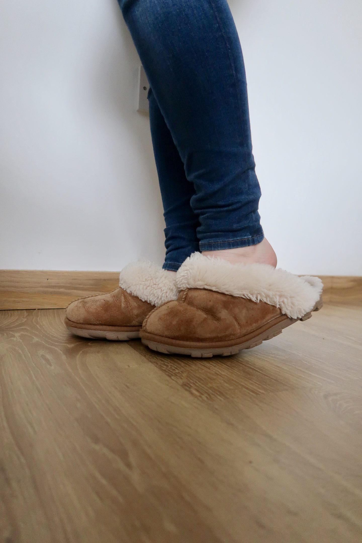 A pair of legs wearing jeans and slippers