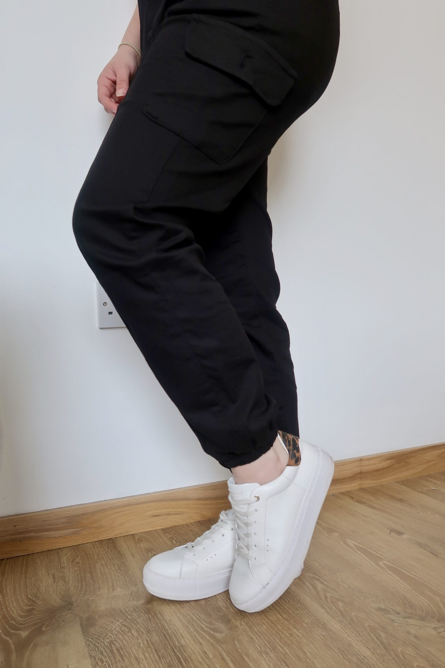 The legs of a woman wearing black cargo trousers and white trainers