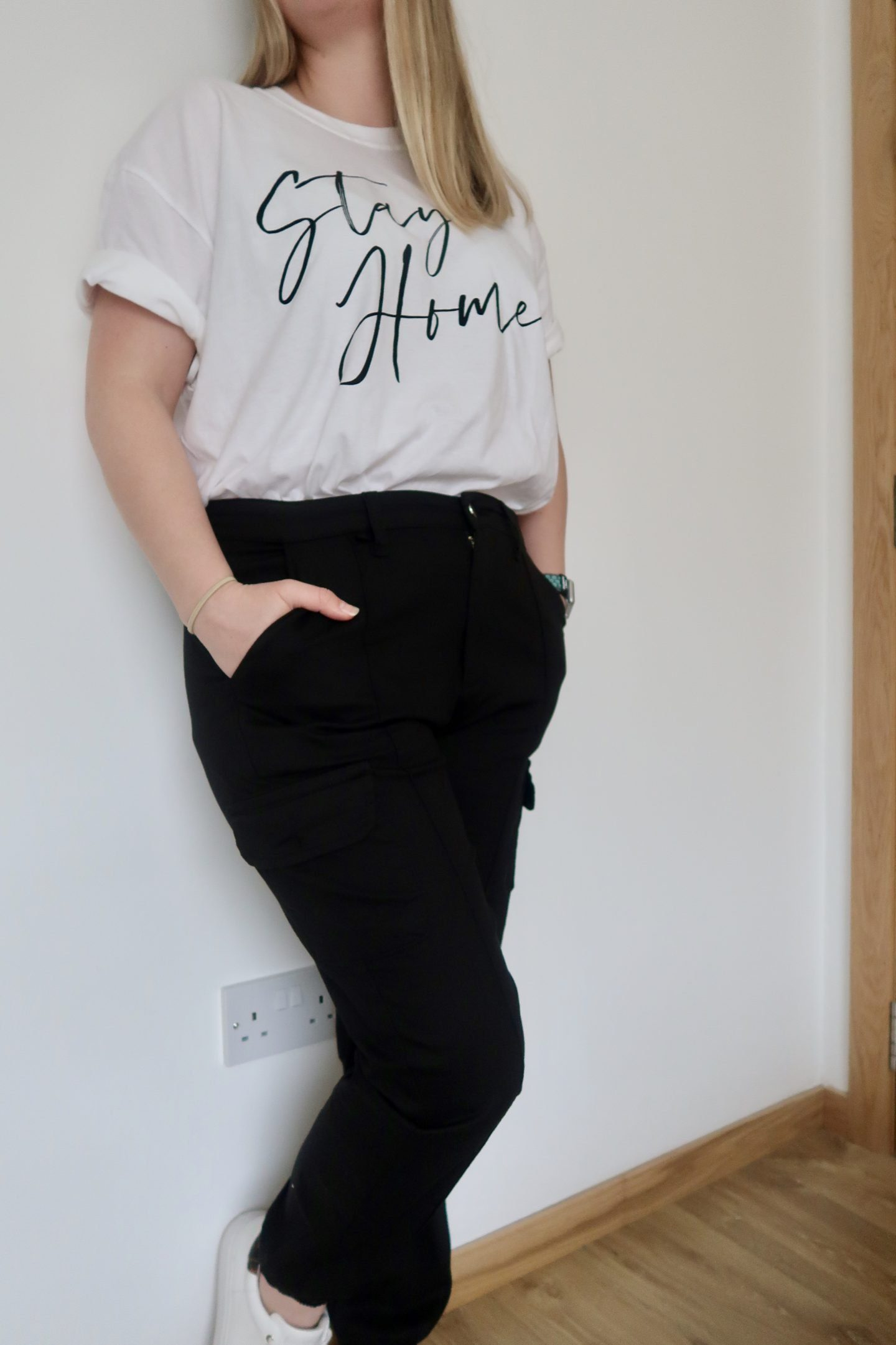 A woman leaning against a wall in a white t-shirt and black cargo trousers