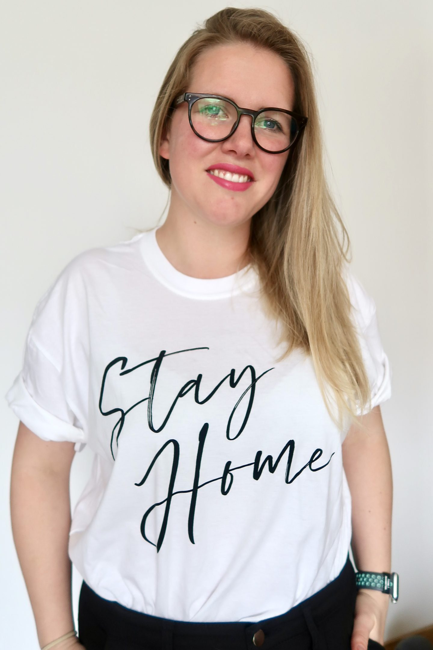 "A woman wearing a white t-shirt with ""stay home"" written on it. She has blonde hair and glasses and is smiling"
