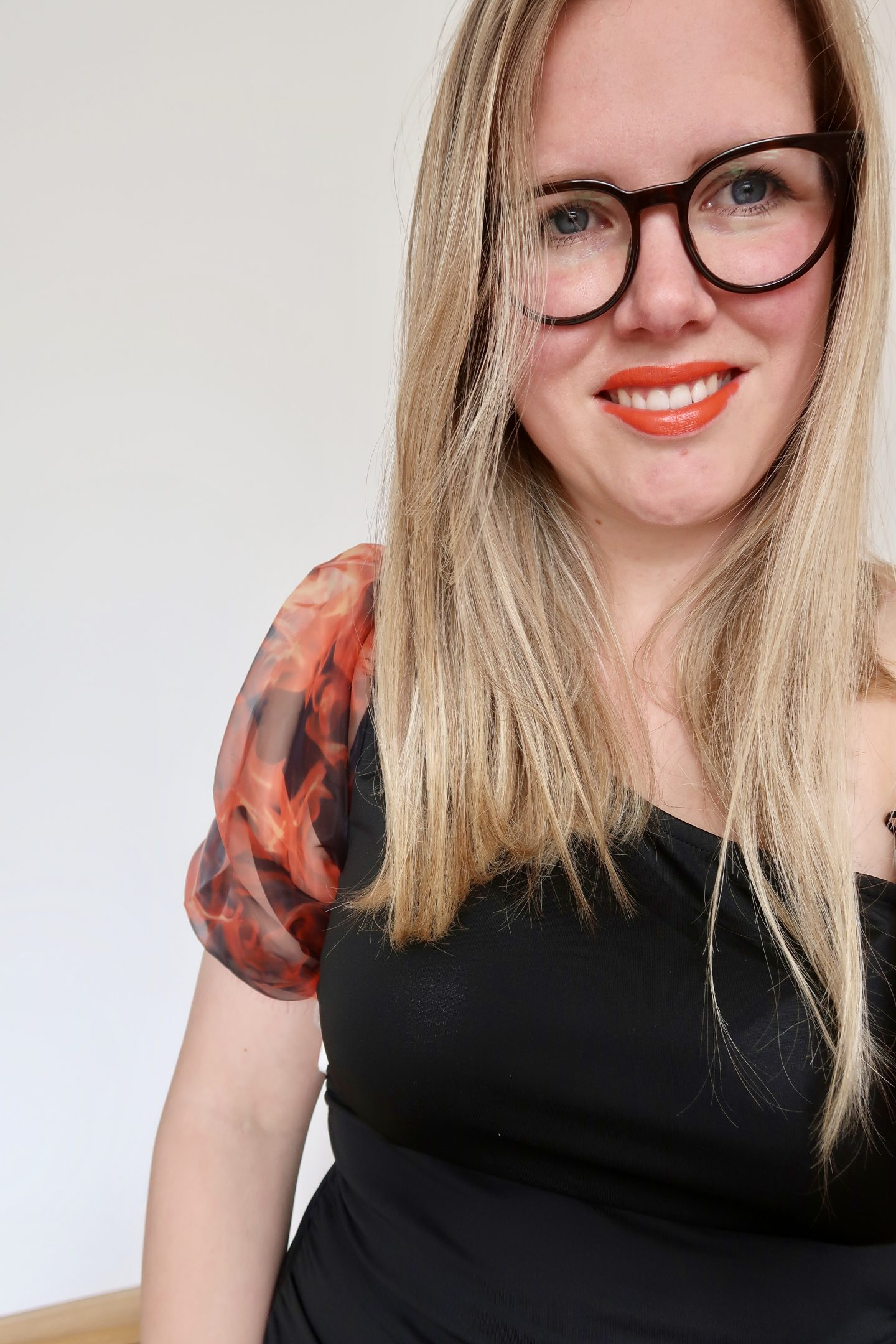 A woman with blonde hair and glasses in a black dress with one sleeve orange and black