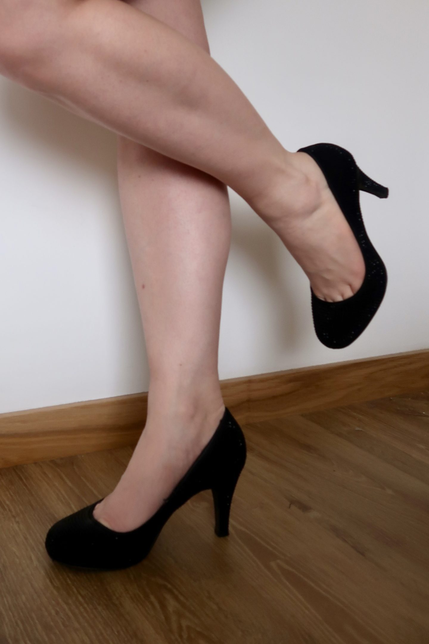 The bare legs of a woman wearing black heeled shoes
