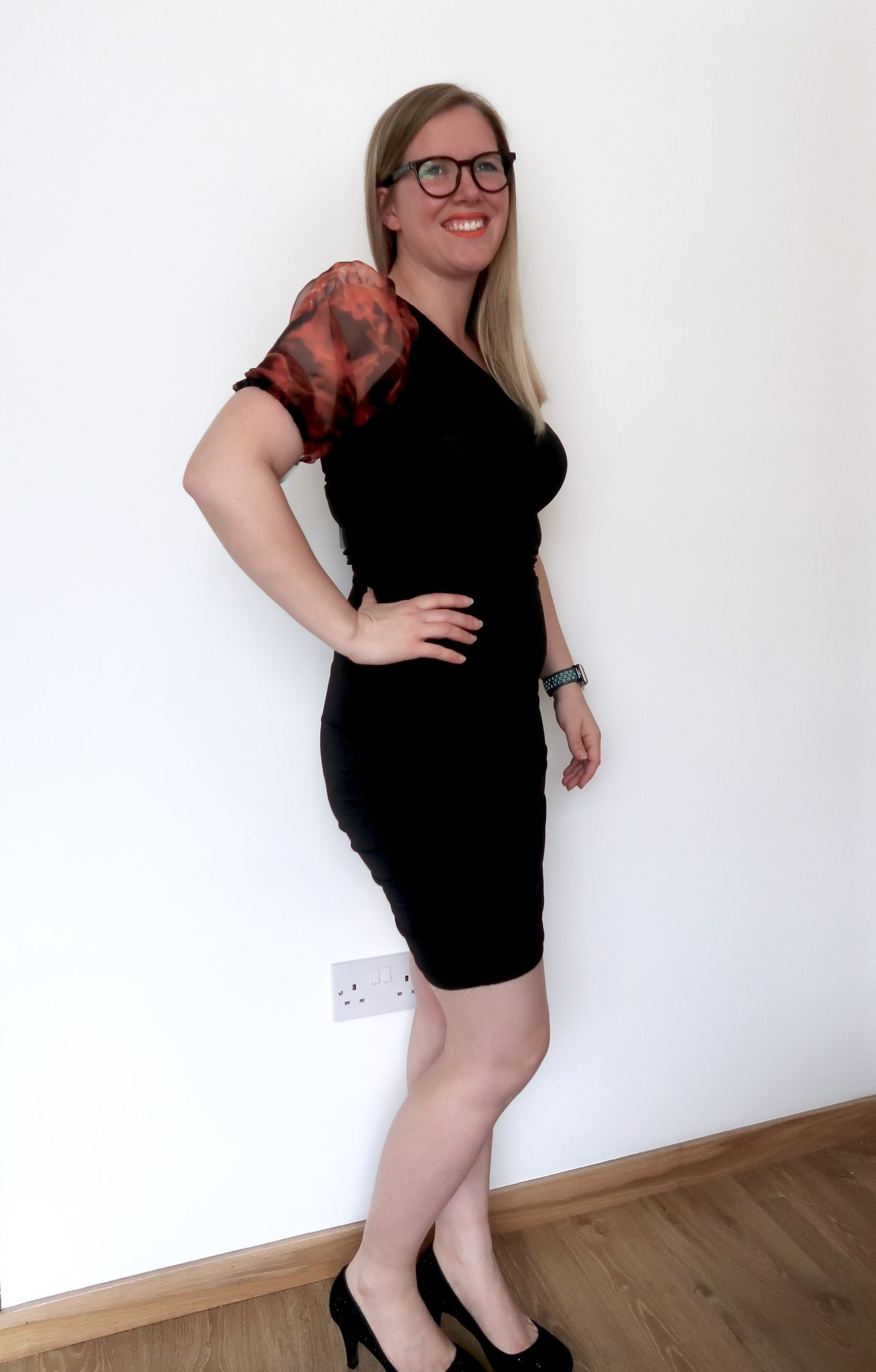 A woman in a one shoulder black dress