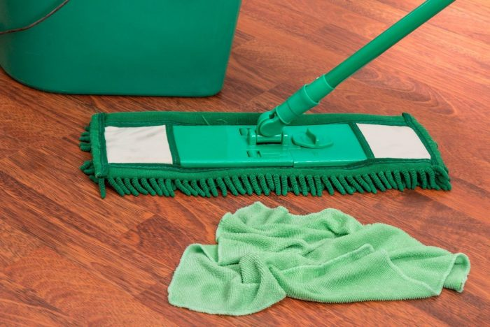 A green cloth, bucket and mop on a wooden floor