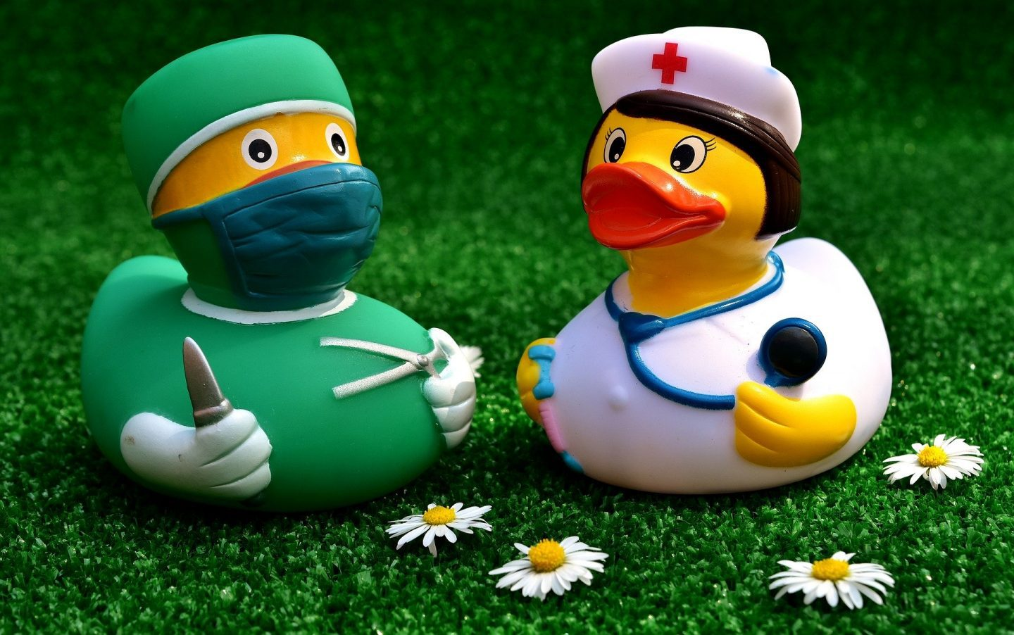 2 rubber ducks, one dressed as a surgeon and one dressed as a nurse