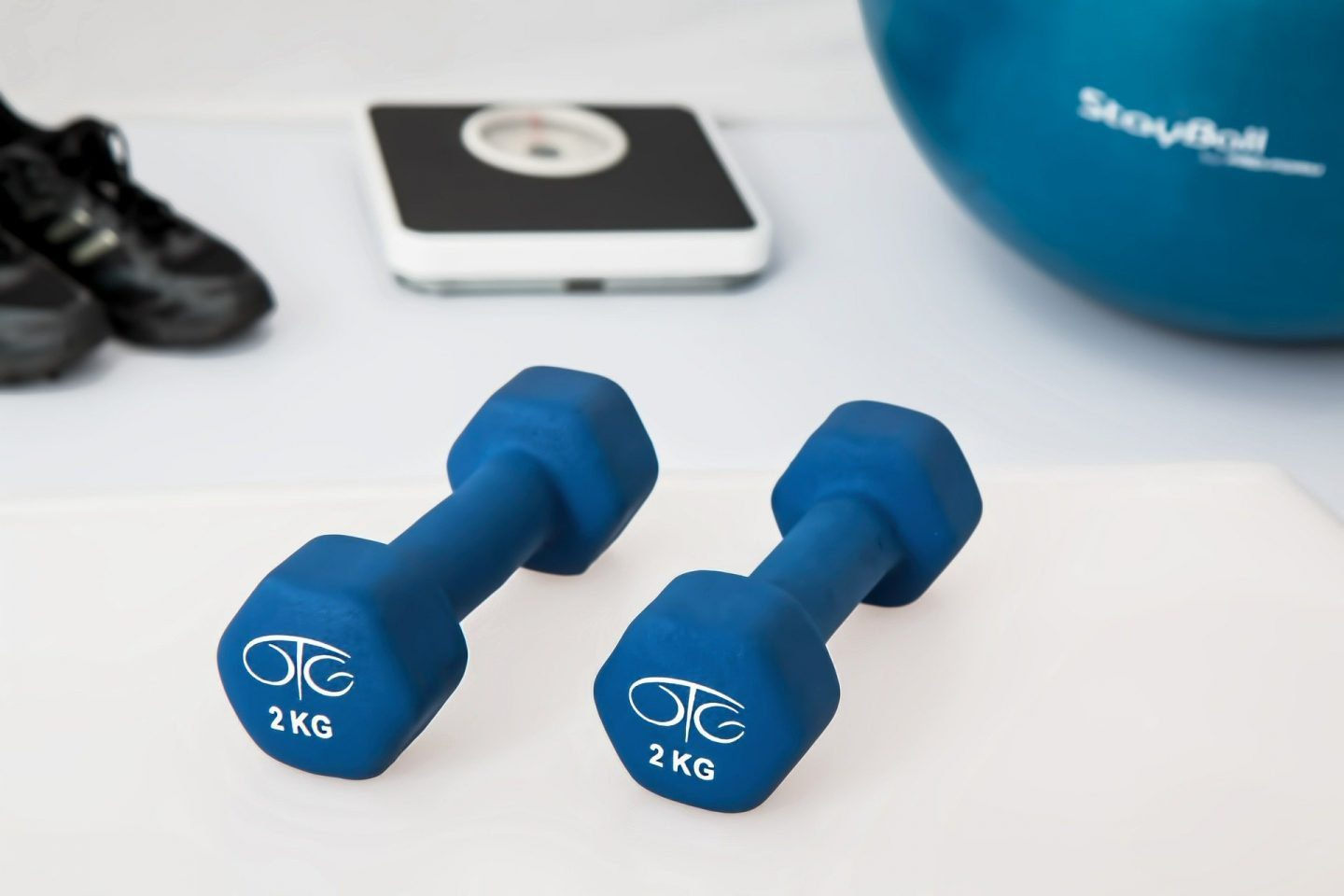 A set of 2kg hand weights, with a set of scales, trainers and yoga ball in the background