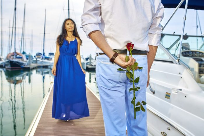 A woman in a blue dress stands in a marina facing the camera. A man stands closer to the camera, facing the woman and holding a rose behind his back.
