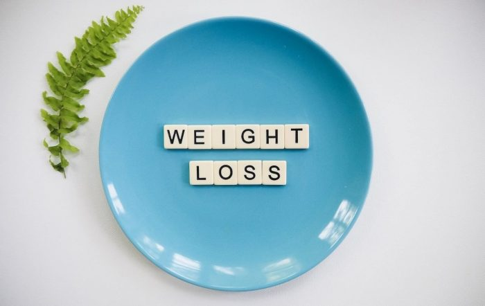 """A blue plate with """"weight loss"""" on it in scrabble letter tiles."""
