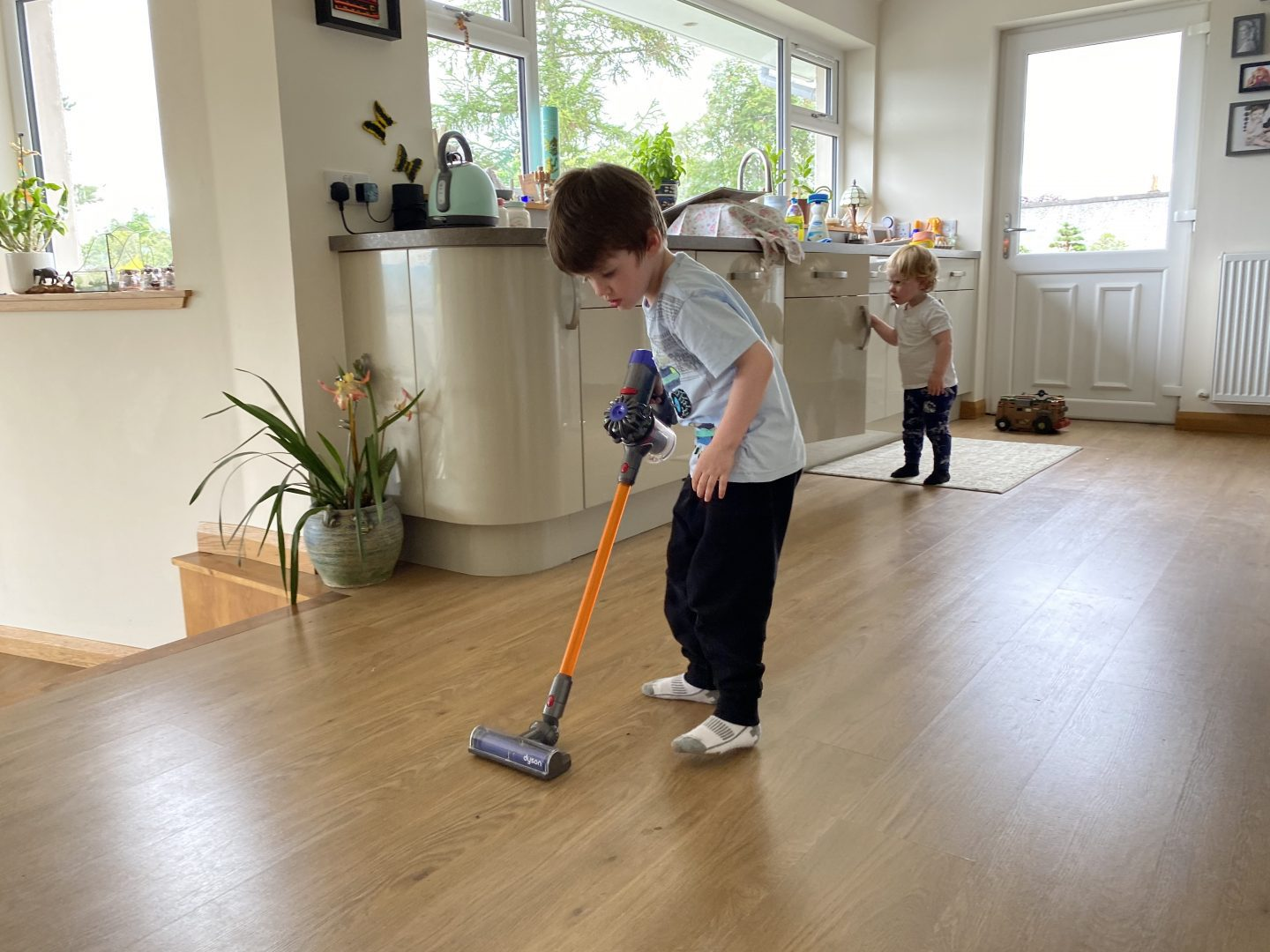 A boy in a kitchen using a toy Dyson cord-free vacuum cleaner