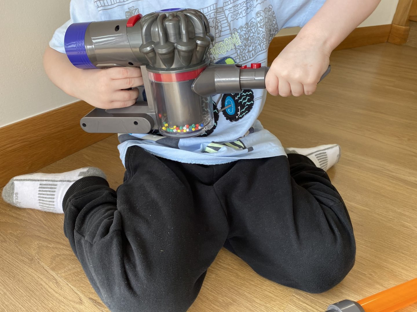 A boy playing with a toy vacuum cleaner