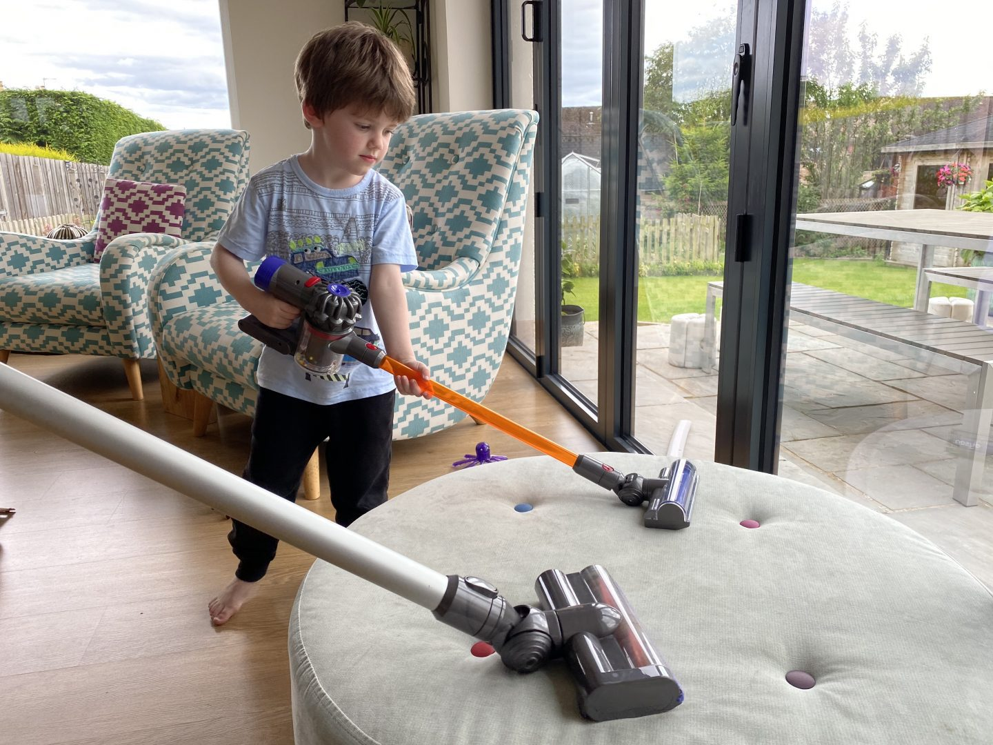 A boy using a toy Dyson cordless vacuum cleaner alongside a real one