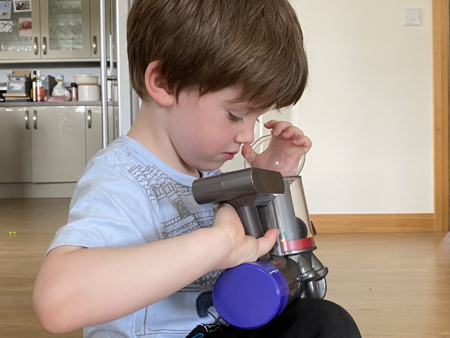 A boy looking into the dust compartment of a toy Dyson