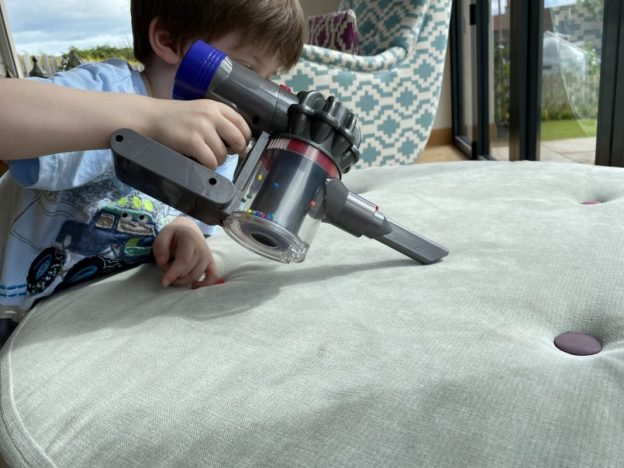 A boy hoovering a seat with a toy cordless vacuum cleaner