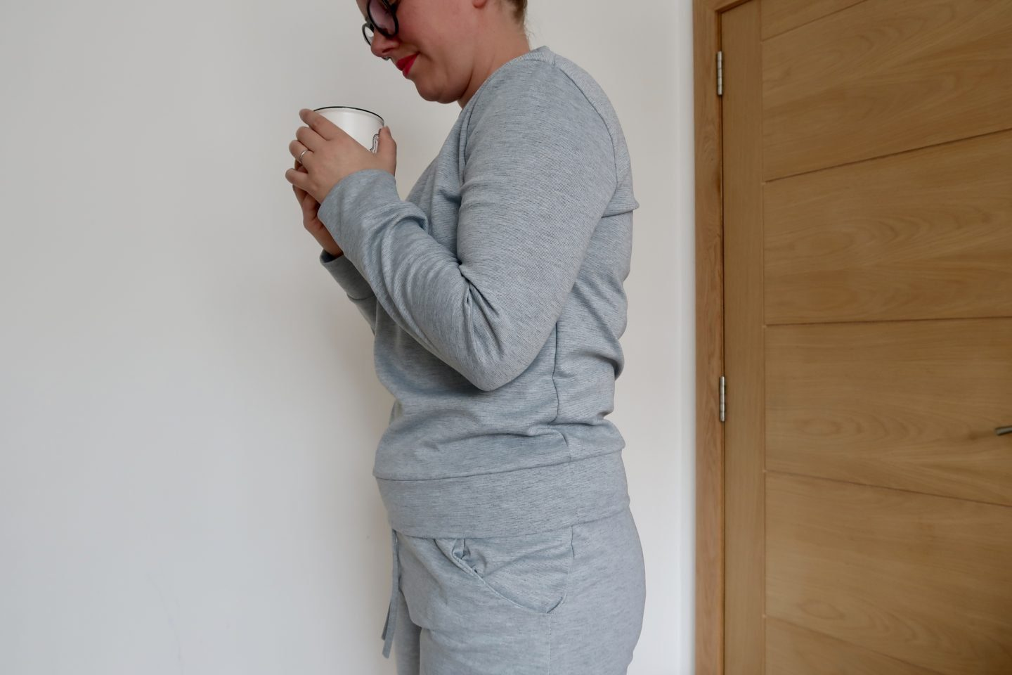 A woman wearing a grey tracksuit holding a mug with both hands