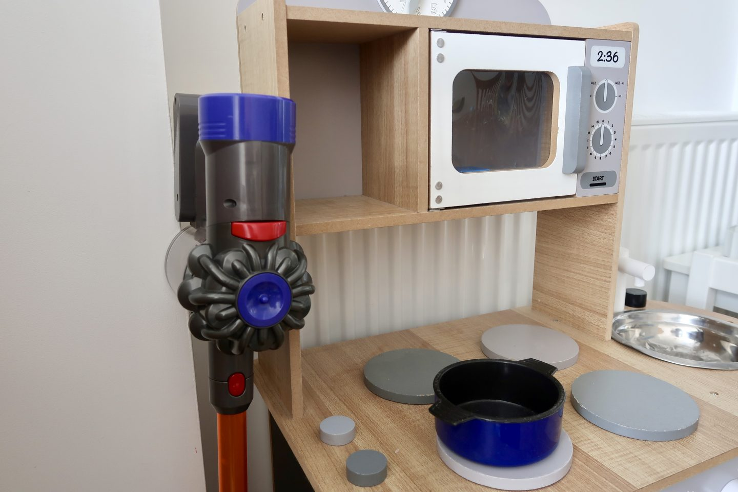 a kids toy Dyson cord-free vacuum cleaner next to a toy kitchen