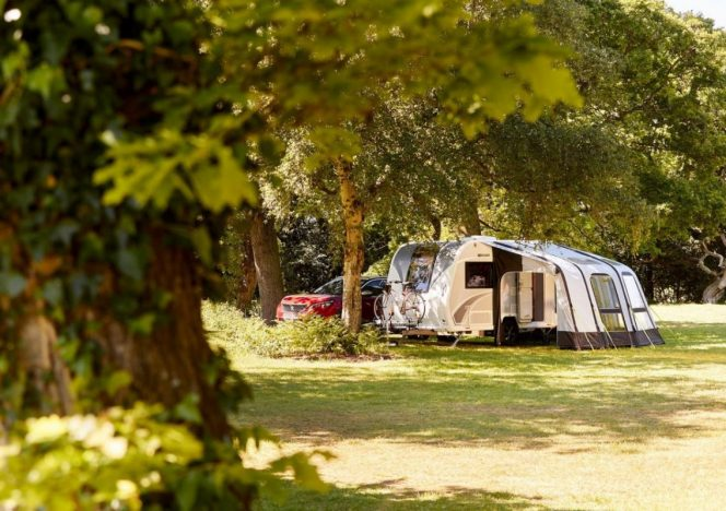 A Bailey caravan set up with it's awning next to some trees