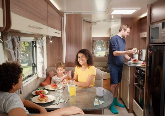 A family inside a caravan making pancakes with strawberries
