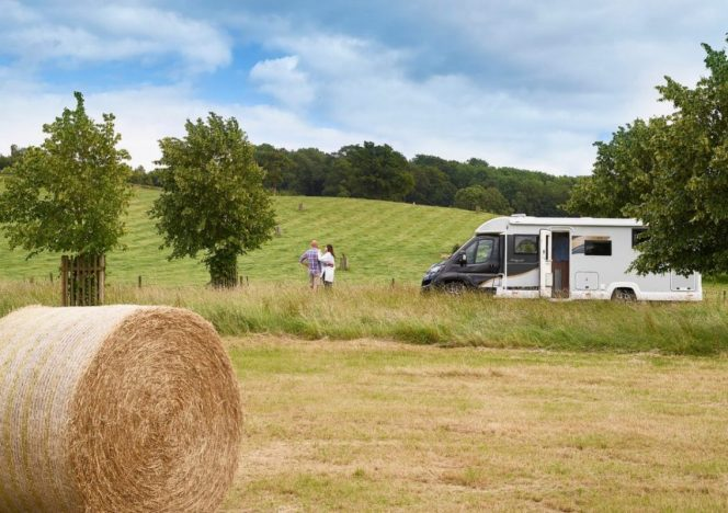 A Bailey campervan at the back of a field. A hay bale is near the front and a couple are standing next to the motorhome