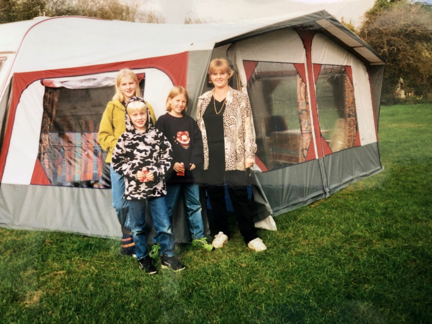 A family standing outside the awning of their caravan in the early 2000's