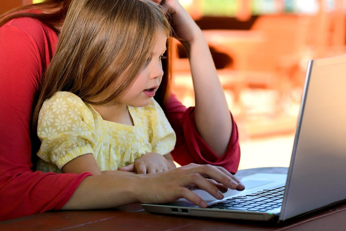 A little girl sitting on her mothers knee and working at a laptop