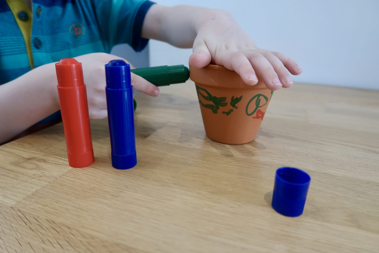 A child decorating a small clay plant pot with pant sticks