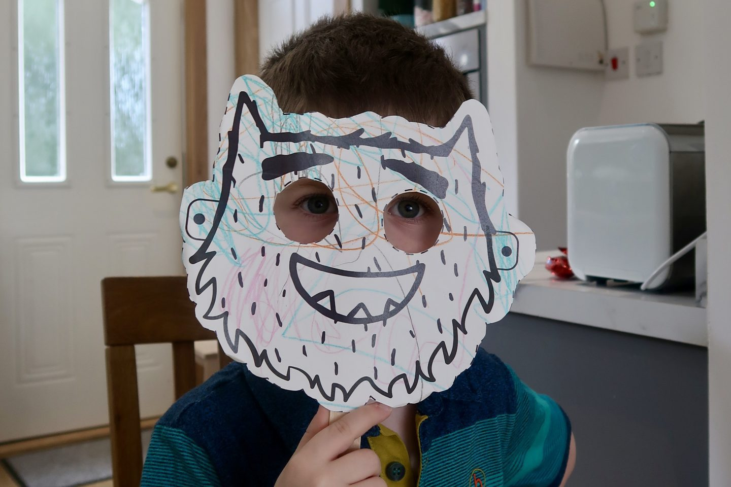 A child holding up a coloured in mask of a monster