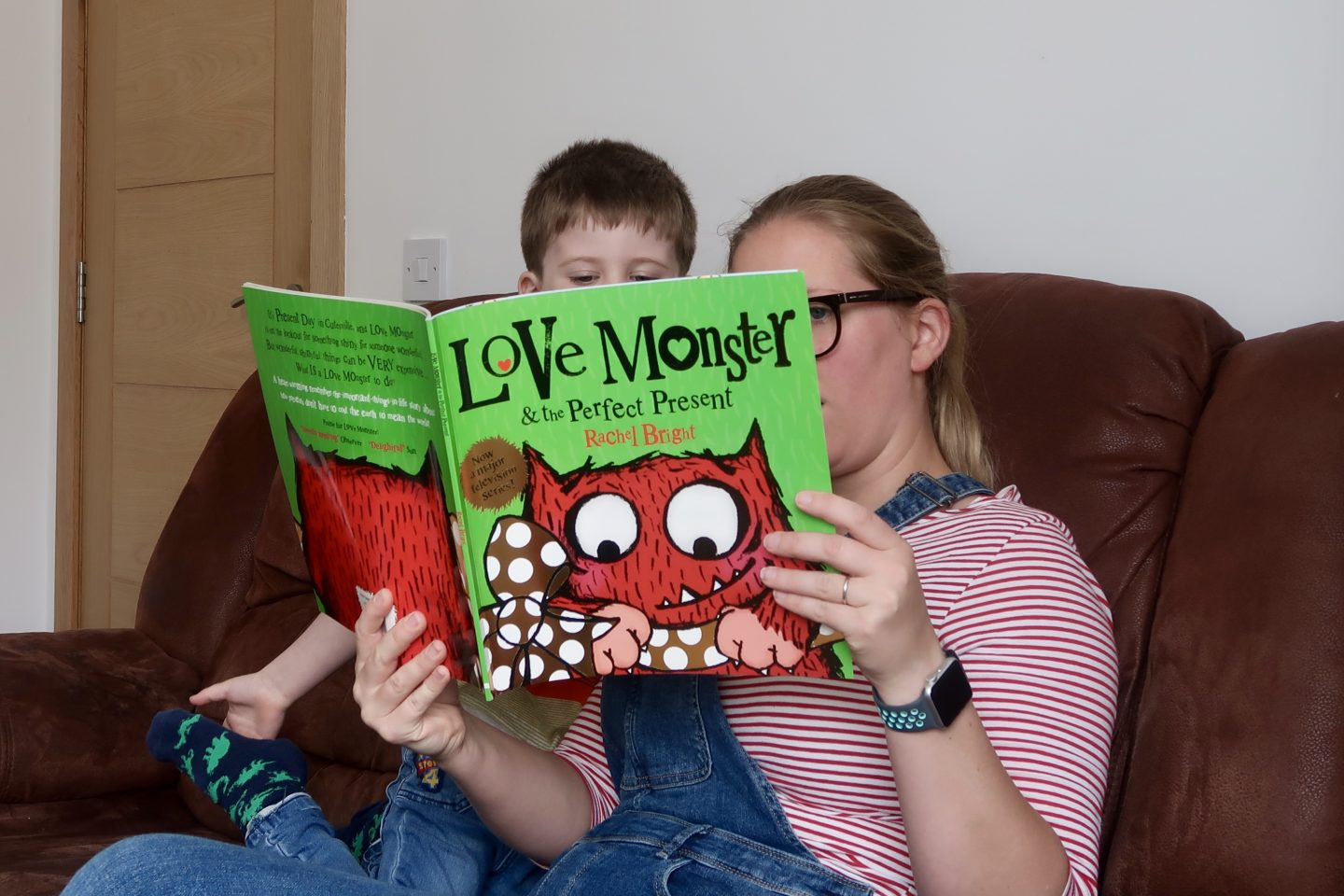 A woman reading a book to a boy. The book is green and has Love Monster written on it, and there is a picture of a red monster