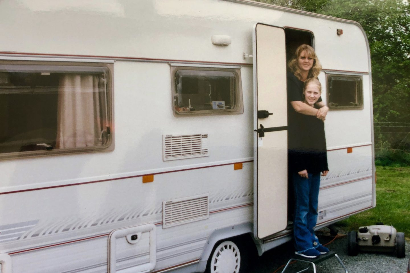 A mother and daughter standing in the doorway of a caravan in the 1990's