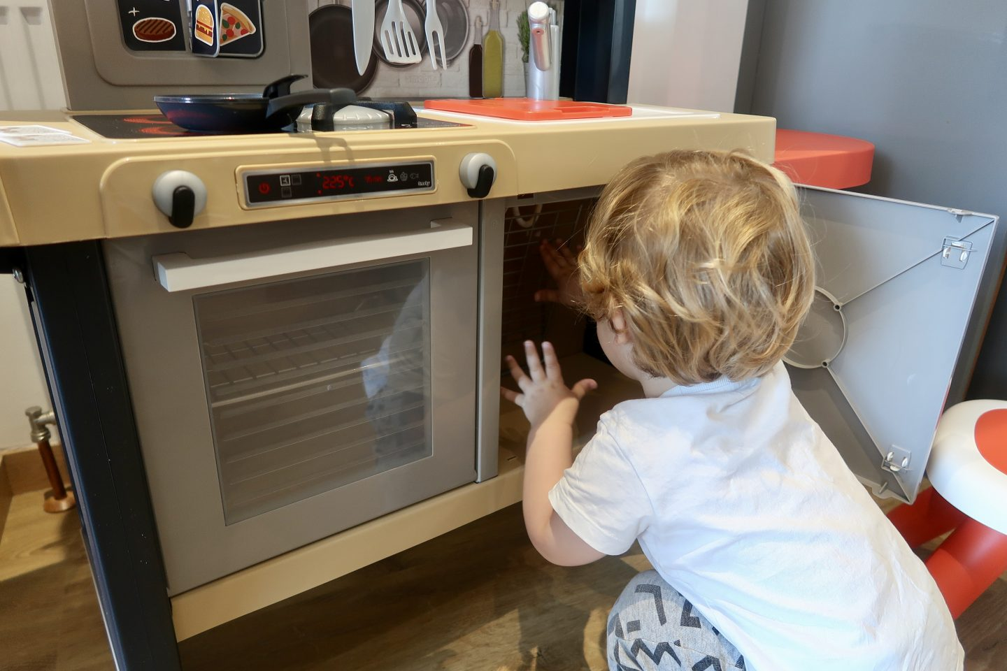 A boy reaching in to the fridge of a toy kitchen