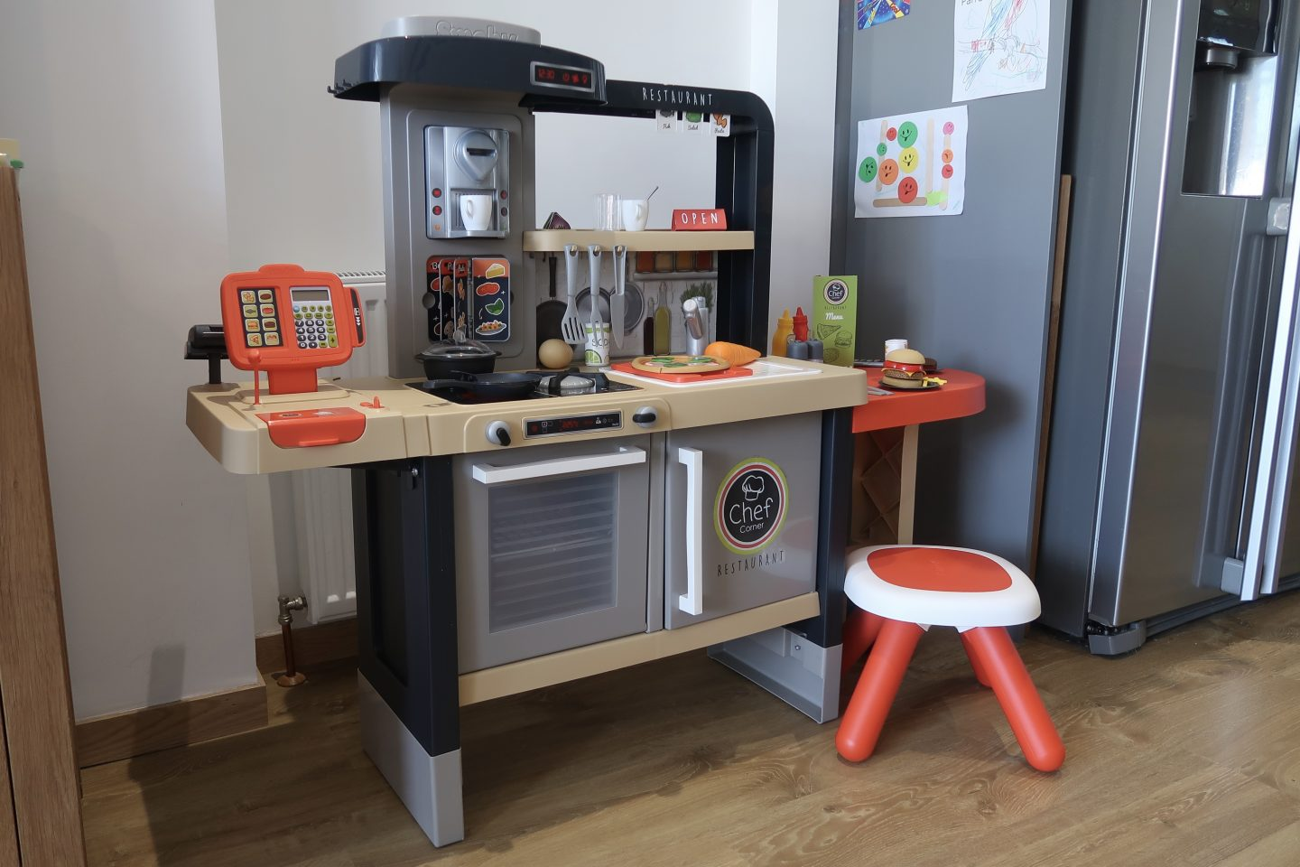 A kids toy kitchen against a wall