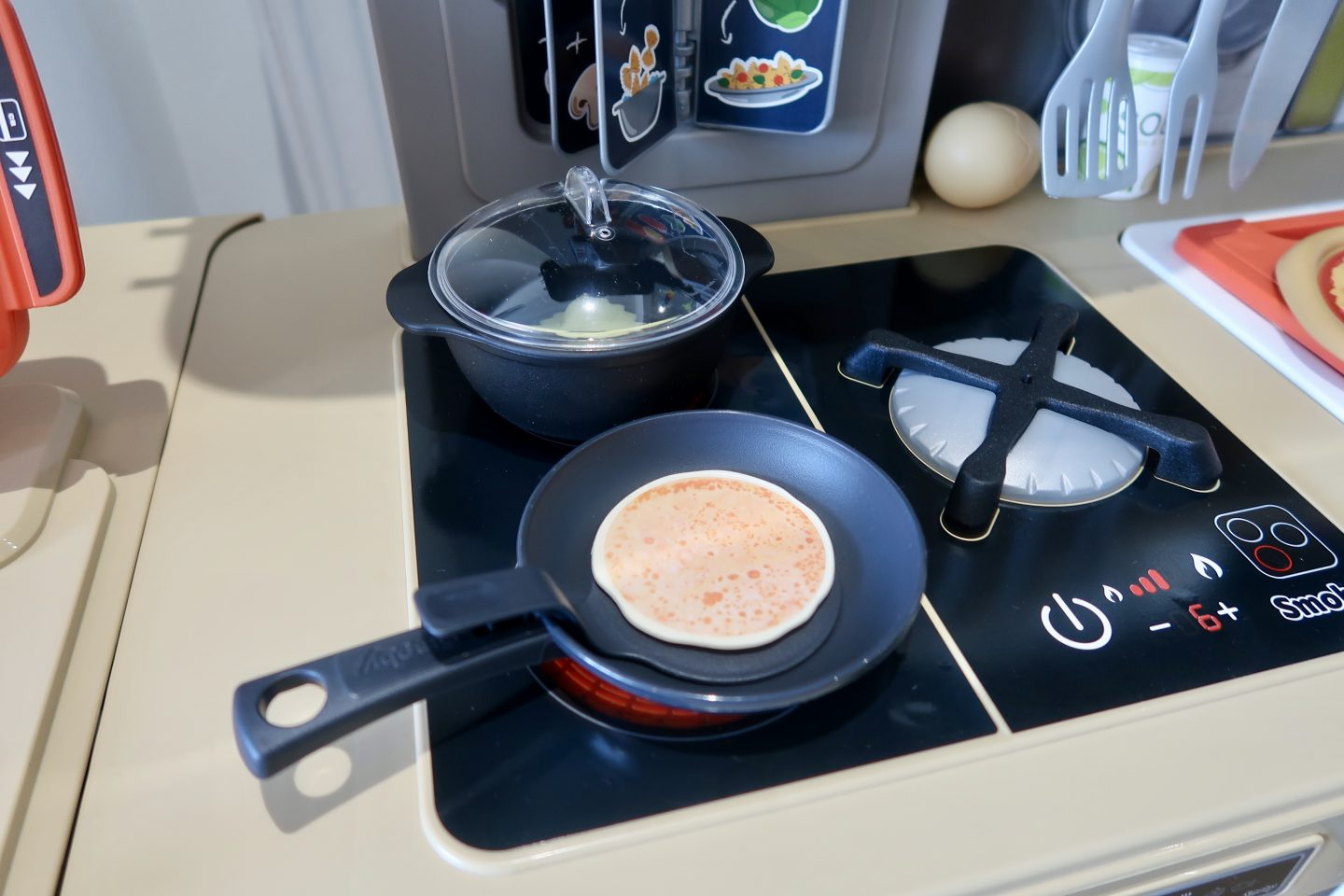 A hob on a plastic kitchen with a frying pan and saucepan on it.