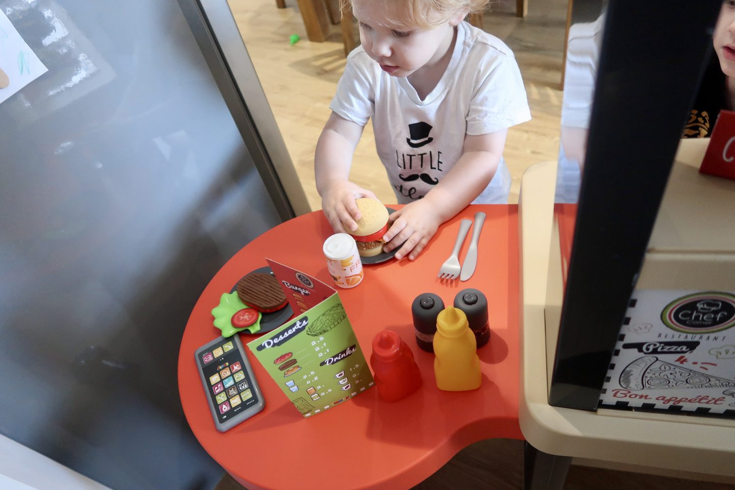 A child sitting at the table of a toy restaurant with a plastic burger and condiements