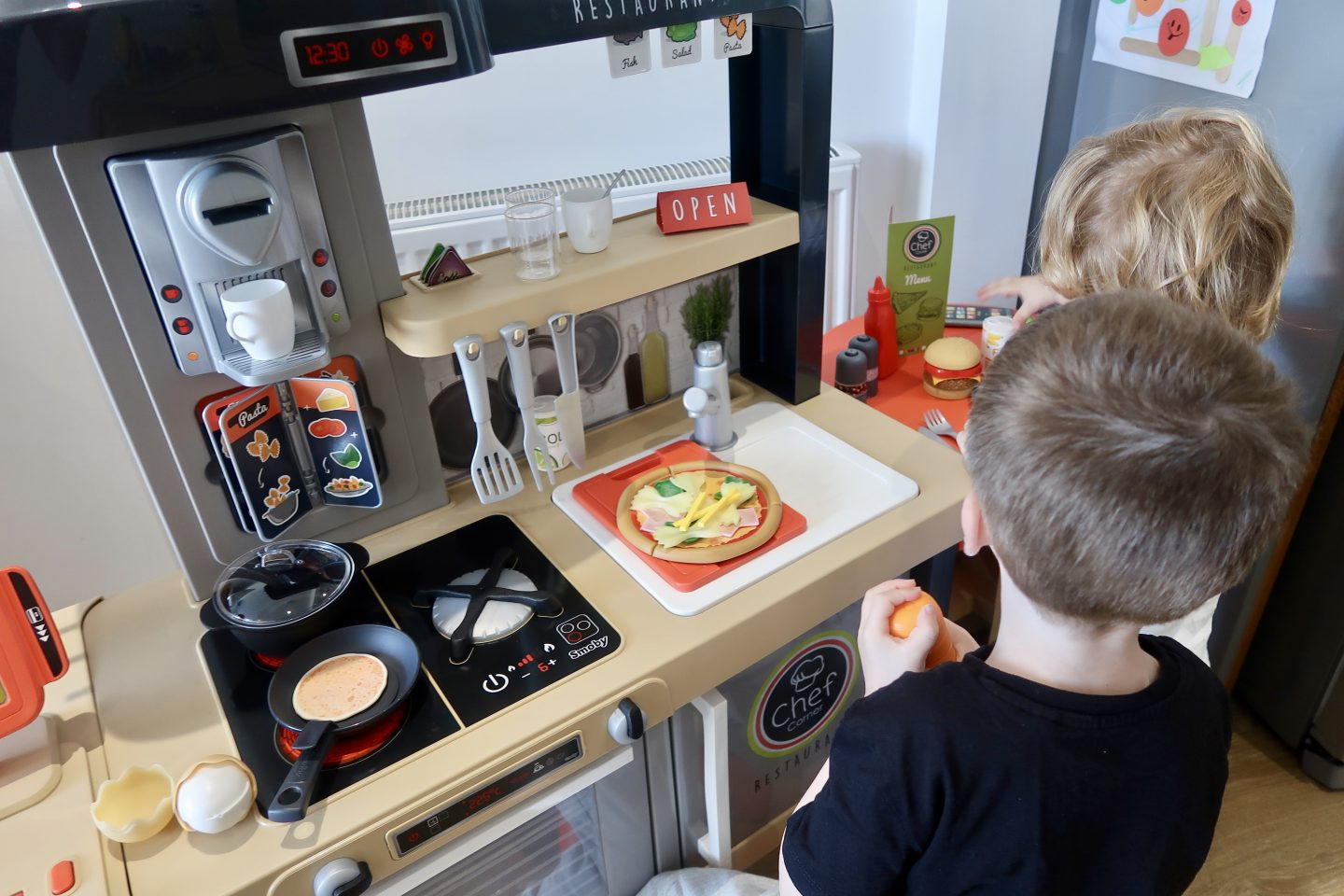 Two boys playing with a Smoby toy kitchen