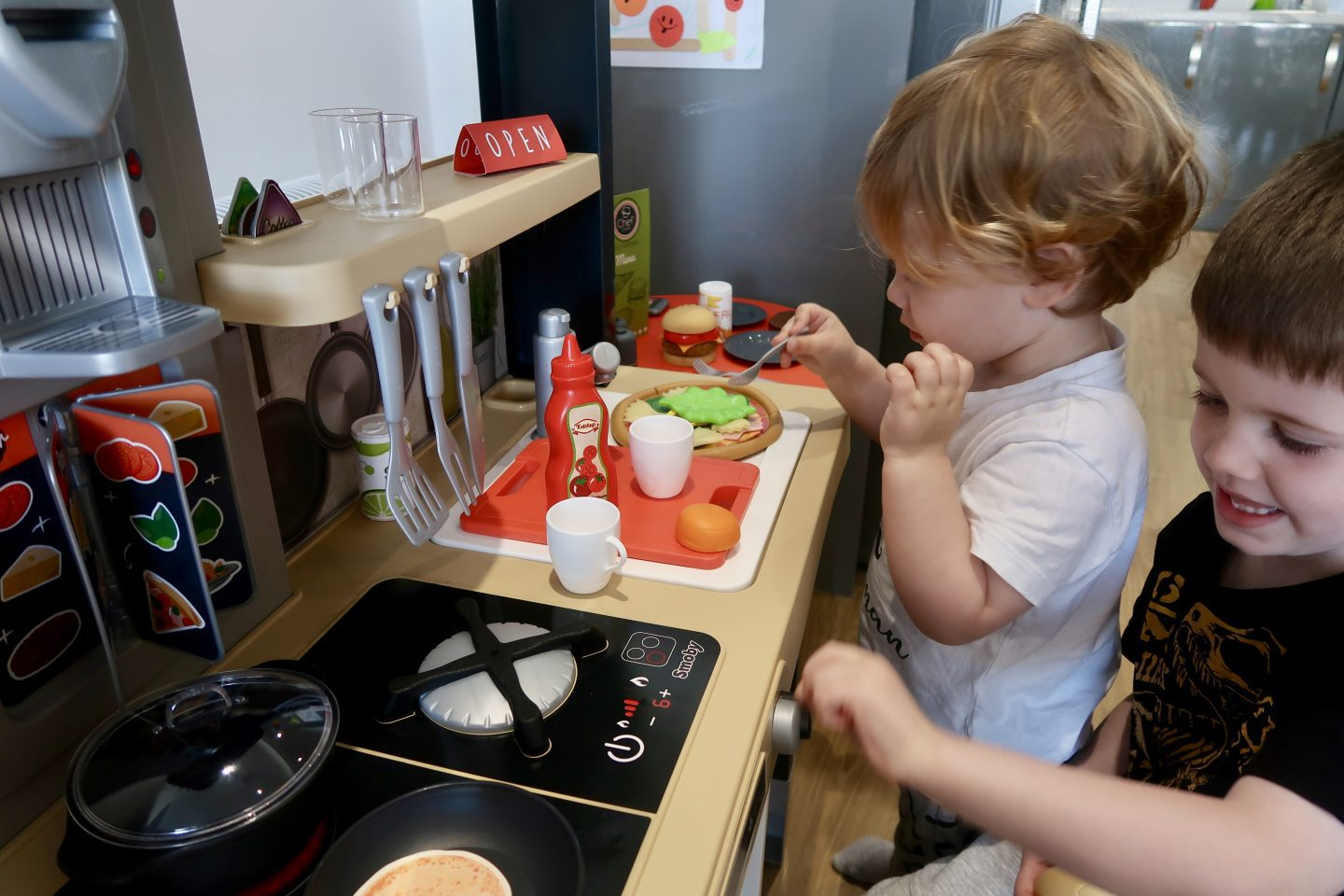 Two children playing with a toy kitchen