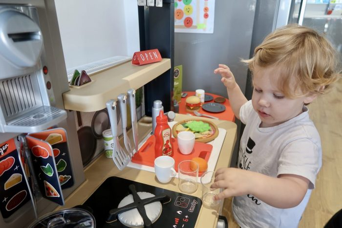 A little boy playing with a plastic Smoby toy kitchen