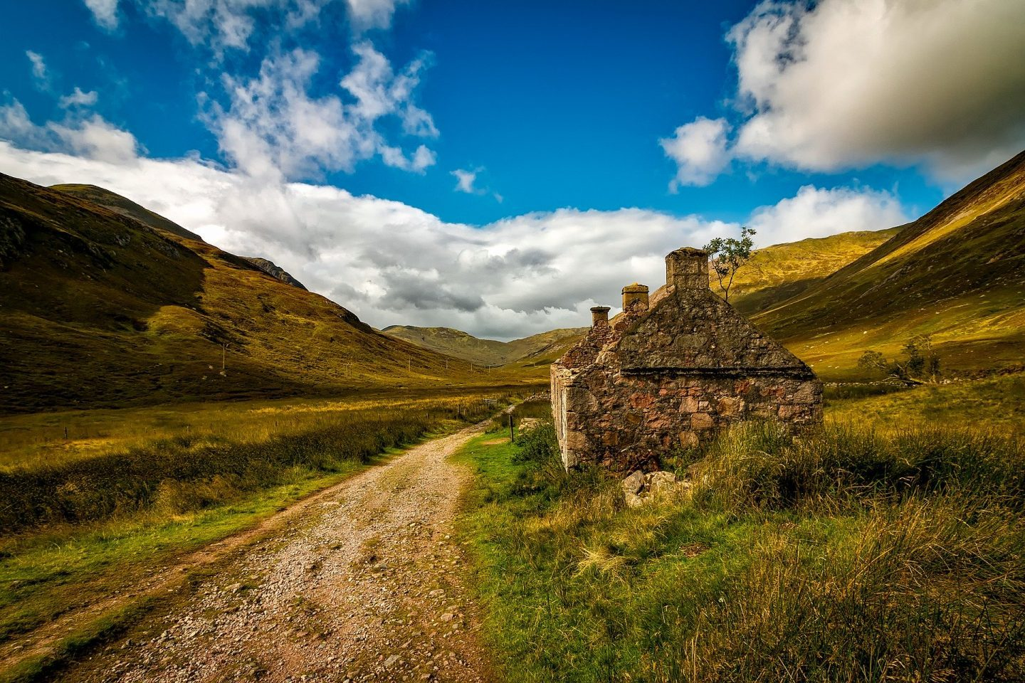 A dirt road in rural Scotland with an abandoned stone cottage