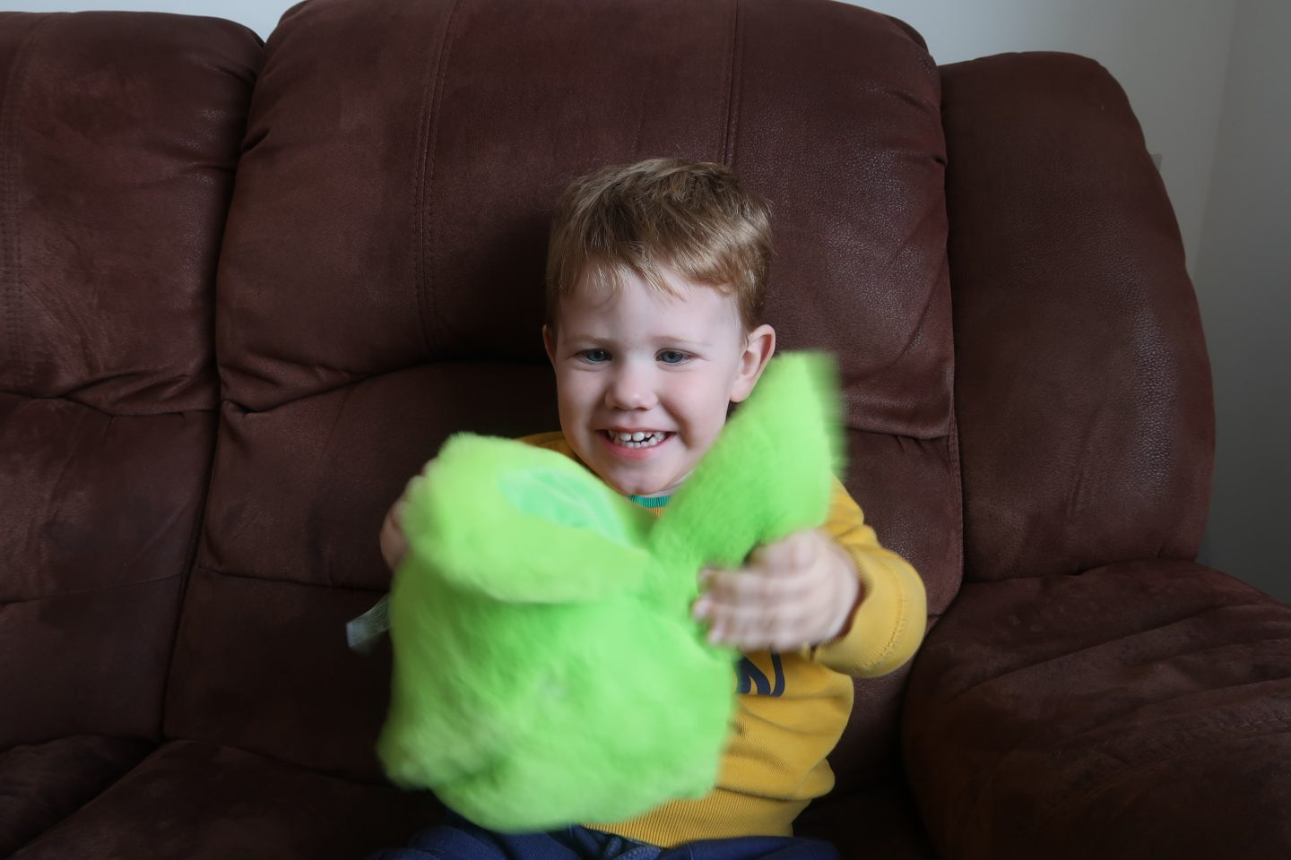 A young boy sat on a brown sofa and holding a green fluffy toy out in front of him. He is smiling at the toy