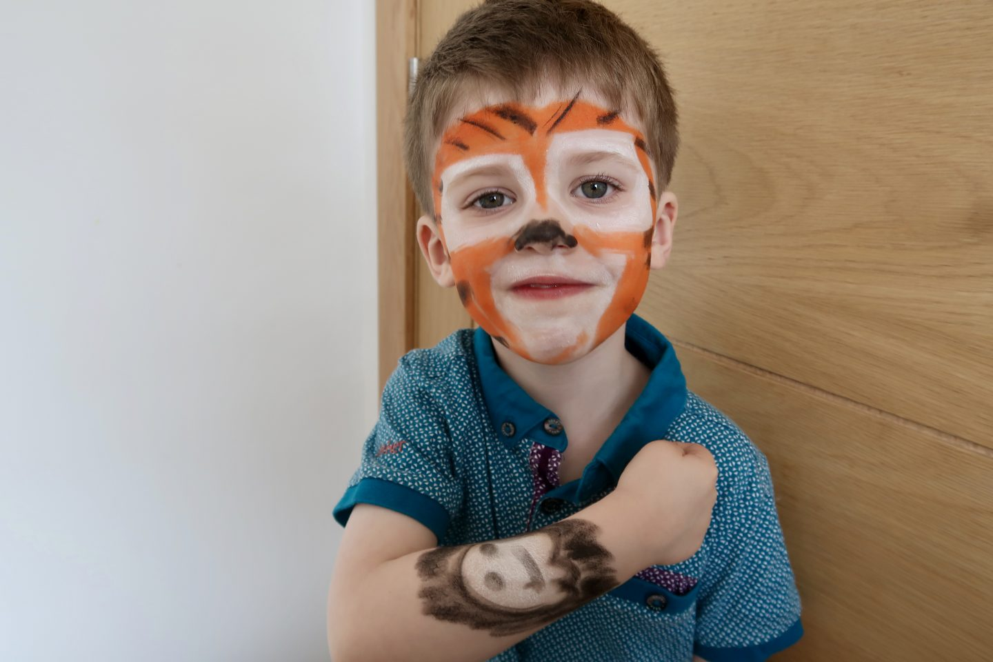 A little boy with his face painted as a tiger and a ghost painted on his arm.
