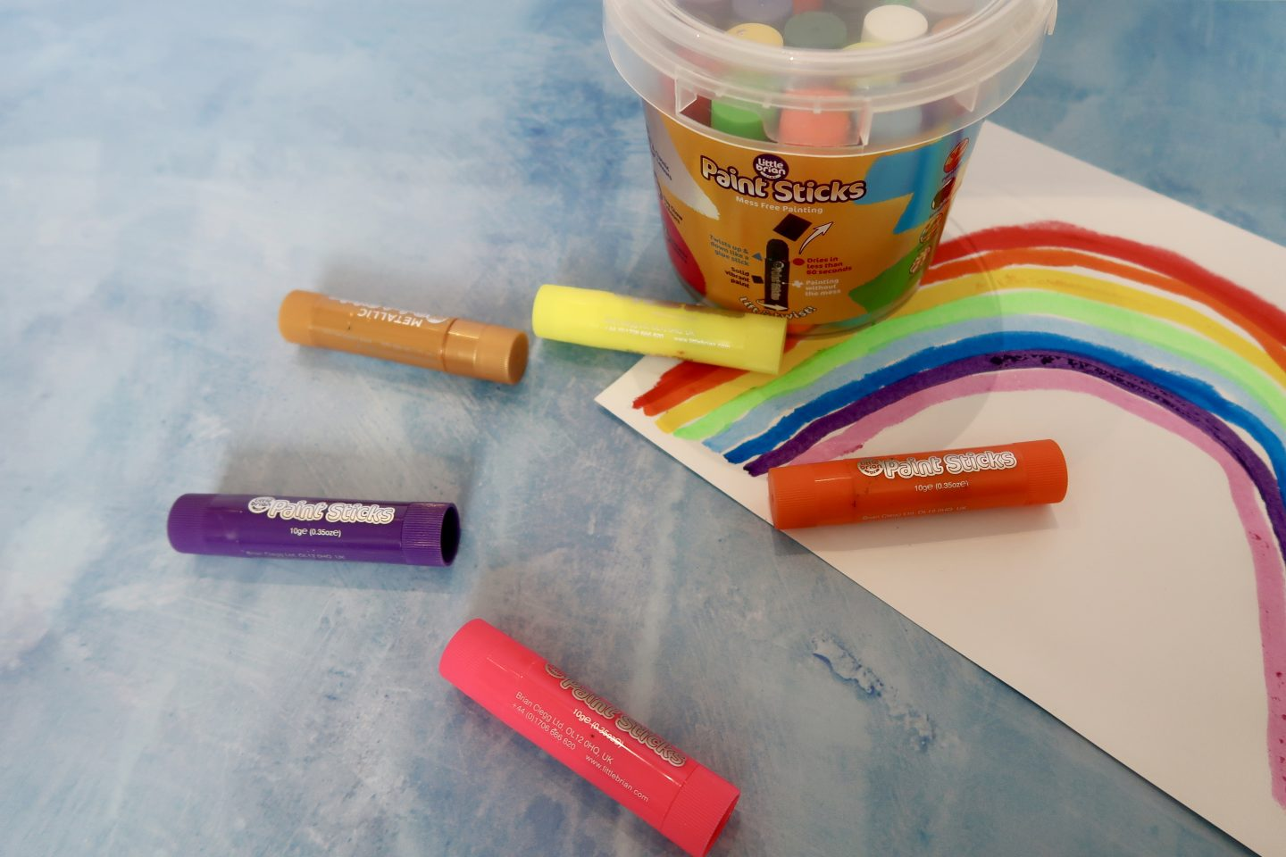 A bucket of paint sticks next to a piece of paper with a rainbow on it