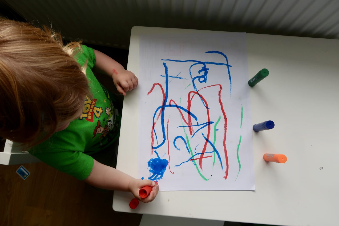 A top down view of a little boy at a small table drawing on paper with paint sticks
