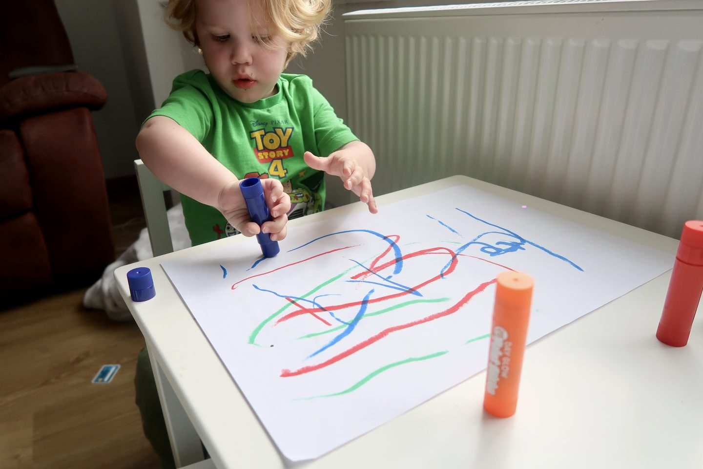 A toddler at a little table painting on paper with paint sticks