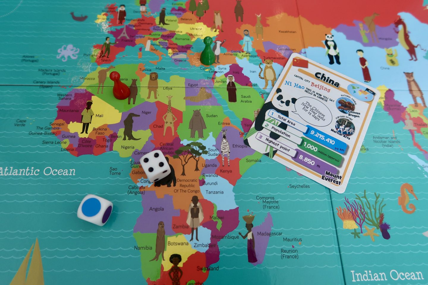 A board game with a world map on it with multicoloured countries