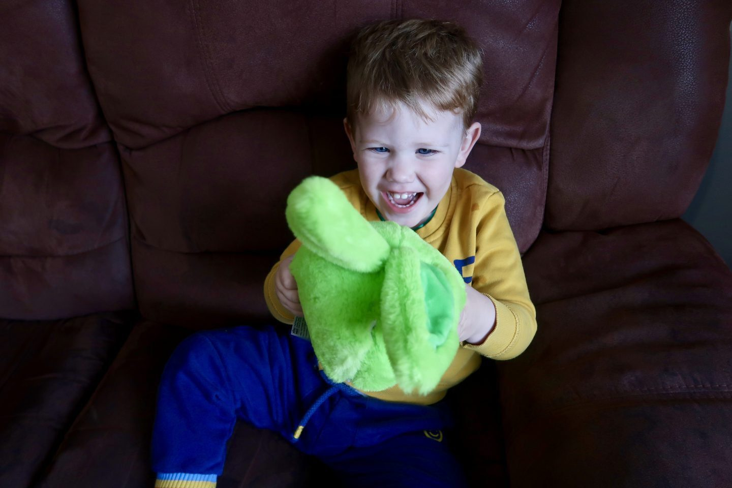 A toddler laughing at a green fluffy toy in his hands