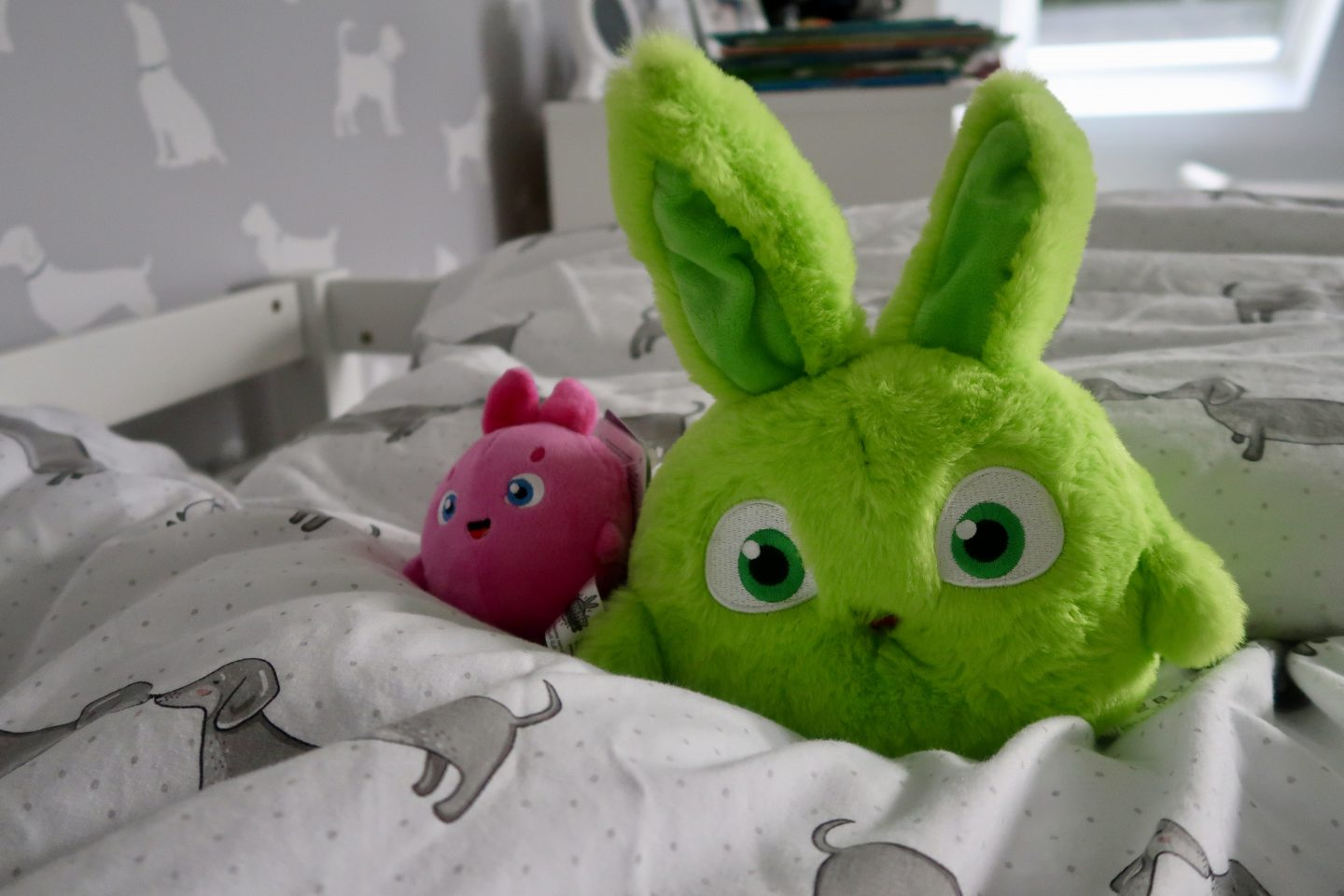 A large green Sunny Bunnies and a small pink Sunny Bunnies sitting on a child's bed