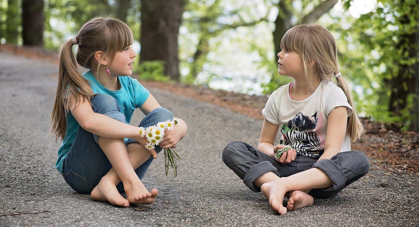 2 girls sitting cross legged on the ground on a path. The are both holding flowers and looking at each other.