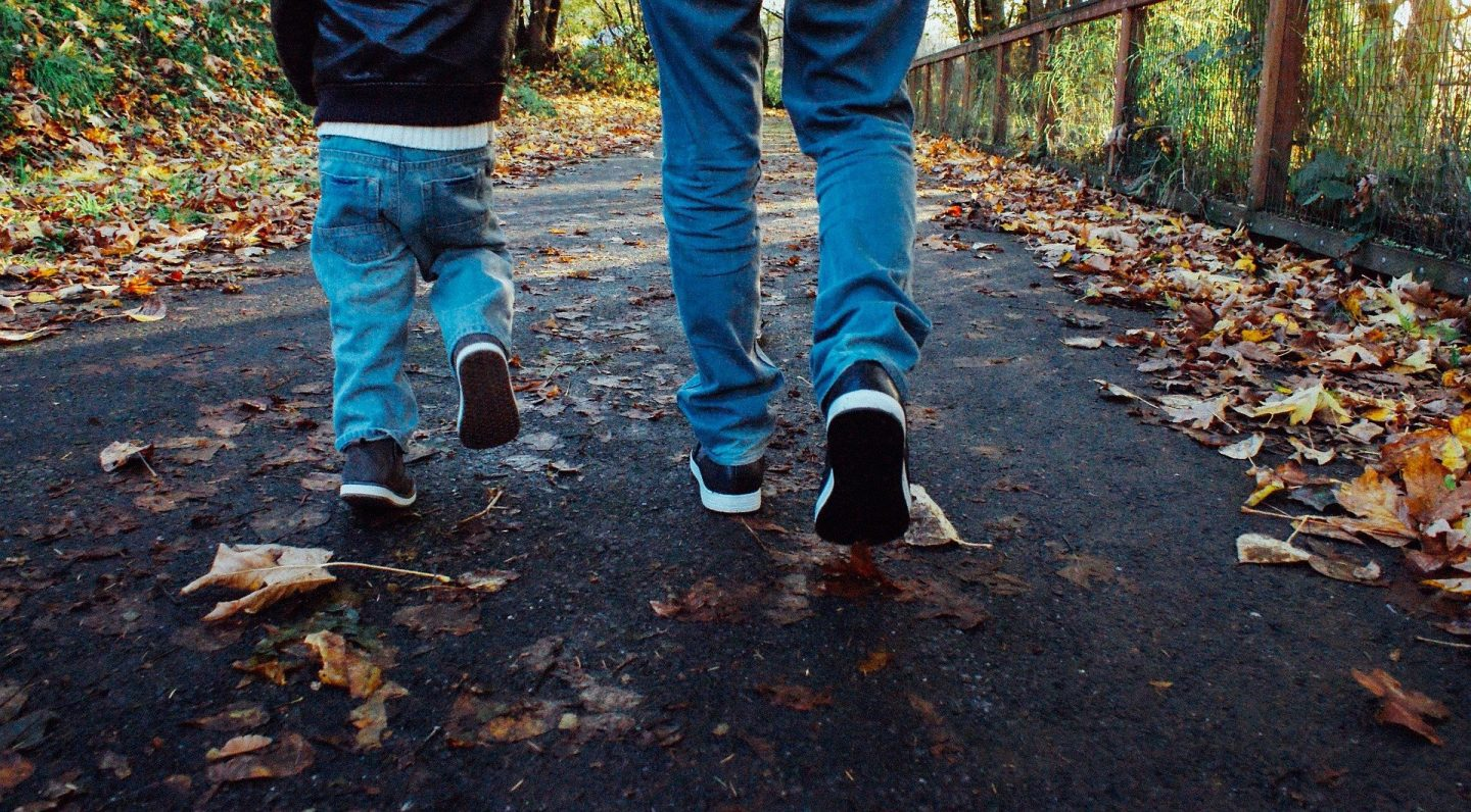 The legs and feet of a man and a child, walking away from the camera through the woods