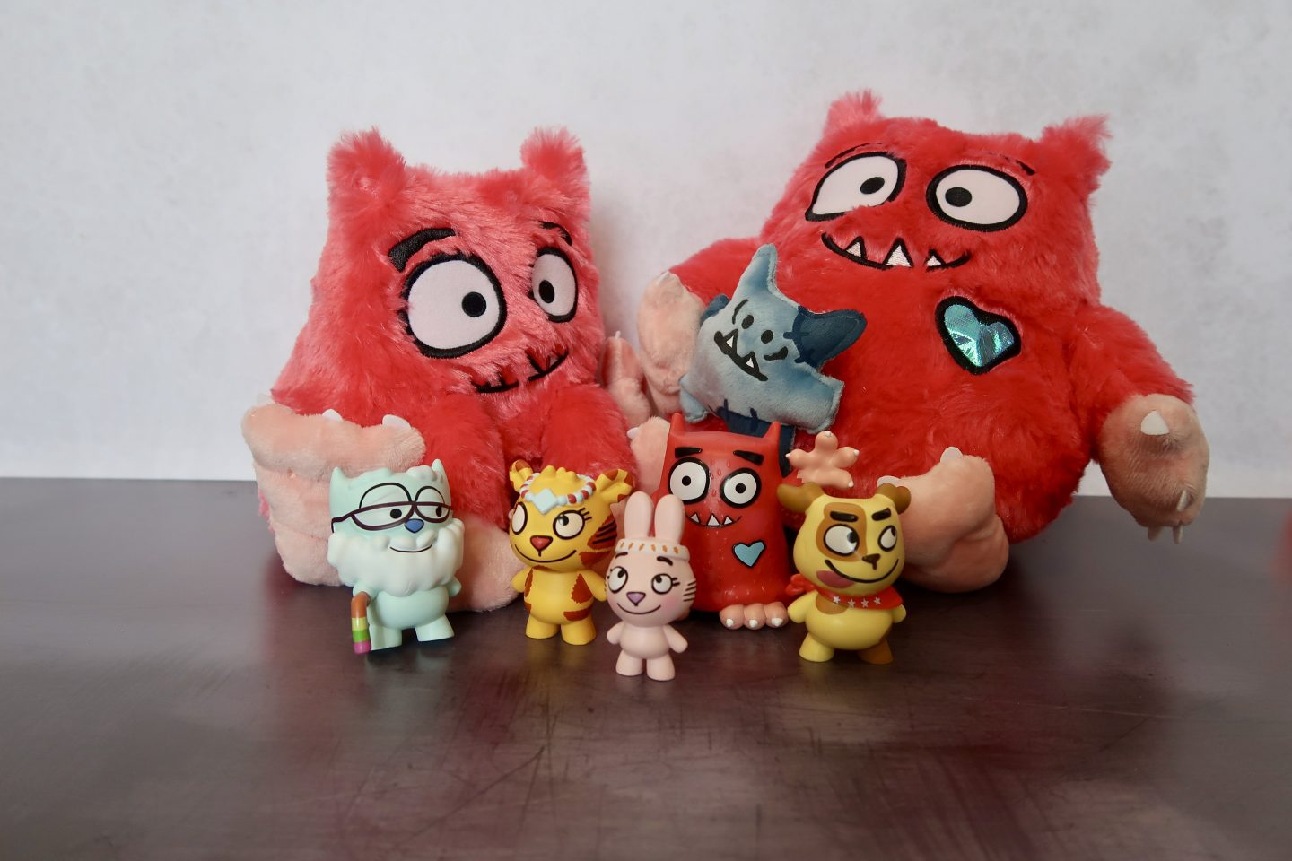 Two stuffed monster toys and 5 little plastic animal figurines