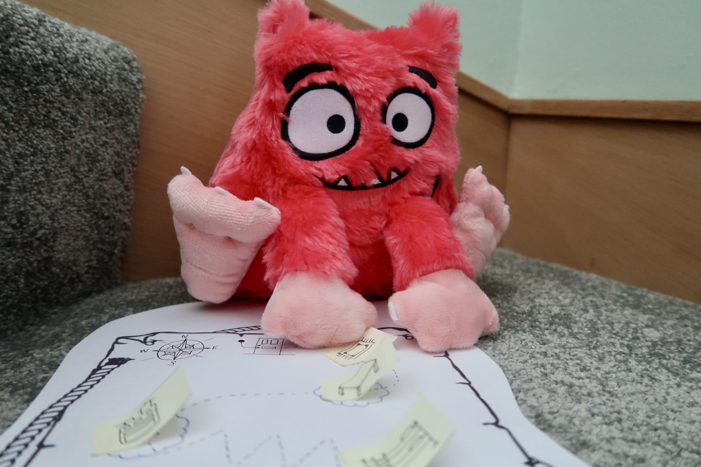 A Love Monster toy sitting with his hands on a treasure map