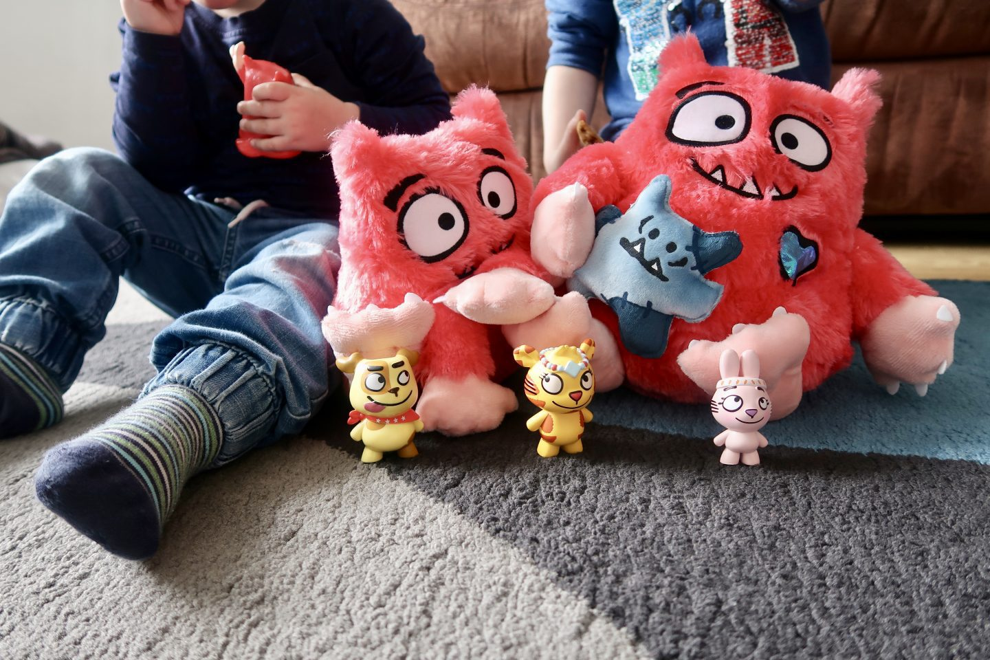 Love Monster toys in front of the bodies of 2 children